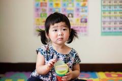 Bambino asiatico sveglio ed innocente con vetro colourful Fotografia Stock