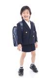 Bambino asiatico in uniforme scolastico con la borsa di scuola blu Immagini Stock Libere da Diritti