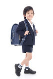 Bambino asiatico in uniforme scolastico con la borsa di scuola blu Fotografia Stock