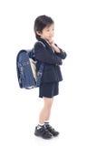Bambino asiatico in uniforme scolastico con la borsa di scuola blu Immagine Stock
