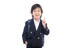 Bambino asiatico in uniforme scolastico con la borsa di scuola blu Fotografia Stock Libera da Diritti