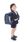 Bambino asiatico in uniforme scolastico con la borsa di scuola blu Immagini Stock
