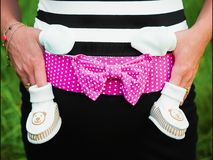 Bambino aspettante, vestiti del bambino per un neonato immagine stock