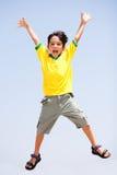Bambino astuto che salta su in aria Fotografia Stock