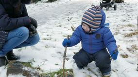 Bambino attraente che gioca con la madre nell'inverno sulla via Il ragazzo nelle mani dei rami degli alberi stock footage