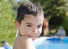 Bambino bagnato sorridente nella piscina Immagine Stock