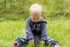 Bambino biondo adorabile sveglio del bambino che si siede su un'erba verde del prato durante il giorno di estate Fotografia Stock Libera da Diritti