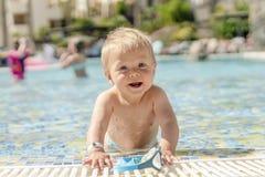 Bambino biondo che gioca con gli occhiali di protezione di nuoto nello stagno immagine stock