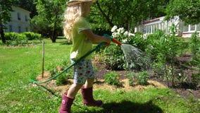 Bambino biondo del giardiniere con il cappello che tiene i fiori dello spruzzatore e dello spruzzo dell'acqua giunto cardanico archivi video