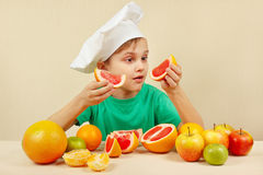 Bambino in cappello dei cuochi unici con due fette di pompelmo alla tavola con i frutti Fotografie Stock Libere da Diritti