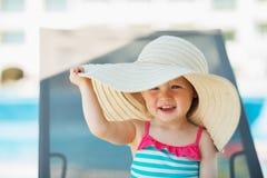 Bambino in cappello della spiaggia che si siede sulla base del sole immagini stock libere da diritti