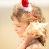 Bambino in cappello di Santa alla spiaggia Fotografia Stock