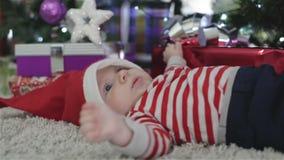Bambino in cappello di Santa che si trova vicino ad un albero di Natale con un regalo stock footage