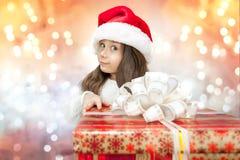 Bambino in cappello di Santa con il contenitore di regalo. Fotografie Stock