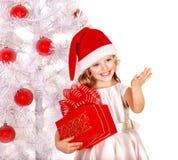 Bambino in cappello di Santa con il contenitore di regalo vicino all'albero di natale bianco. Fotografia Stock