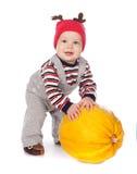 Bambino in cappello divertente dei cervi con la zucca arancione Fotografia Stock