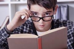 Bambino a casa con il libro, studenti Fotografia Stock