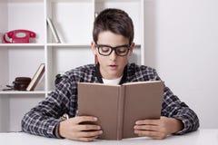 Bambino a casa con il libro, studenti Fotografie Stock