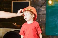 Bambino in casco protettivo, casco a casa in officina Supporti svegli ed adorabili del bambino mentre mettere maschio della mano  fotografia stock