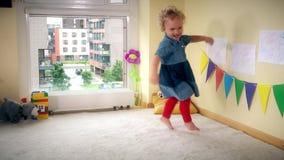 Bambino cattivo a casa Salto attivo e ballo di funzionamento della ragazza con energia video d archivio