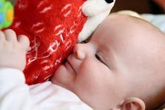 Bambino che abbraccia il grande cuore della peluche Fotografia Stock