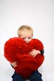 Bambino che abbraccia un cuore della peluche immagini stock