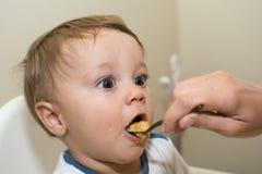 bambino che alimenta la sua madre Fotografie Stock Libere da Diritti