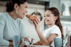 Bambino che alimenta sua madre con un croissant immagini stock