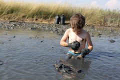 Bambino che applica argilla curativa nera Fotografia Stock Libera da Diritti