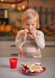 Bambino che assaggia i biscotti casalinghi di natale in cucina Fotografie Stock