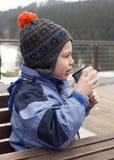 Bambino che beve dalla boccetta nell'inverno Fotografie Stock
