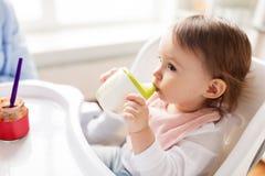 Bambino che beve dalla tazza del becco in seggiolone a casa Immagini Stock Libere da Diritti