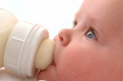 Bambino che beve la sua bottiglia Fotografia Stock