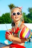 Bambino che beve vicino alla piscina. Immagine Stock