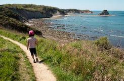 Bambino che cammina su un percorso sopra il mare. Immagini Stock