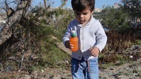 Bambino che cammina verso la macchina fotografica sul litorale con gli alberi stock footage