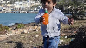 Bambino che cammina verso la macchina fotografica sul litorale con gli alberi archivi video