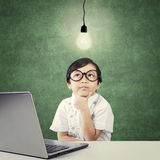 Bambino che cerca lampada con il computer portatile sulla tavola Fotografie Stock Libere da Diritti
