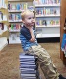 Bambino che cerca un libro sullo scaffale alla biblioteca Immagini Stock