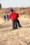 Bambino che cicla a partire dalla macchina fotografica Fotografie Stock