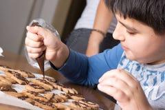 Bambino che compone decorazione sulla fine del biscotto del pan di zenzero Spirito di cottura immagine stock libera da diritti