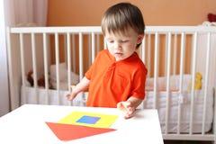 Bambino che costruisce casa con dettagli di carta Immagini Stock Libere da Diritti