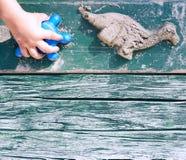 Bambino che crea le forme animali con la sabbia Fotografia Stock Libera da Diritti