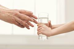 Bambino che dà bicchiere d'acqua al mgrandfather fotografia stock libera da diritti