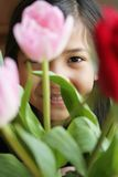 Bambino che dà una occhiata attraverso i fiori Fotografia Stock