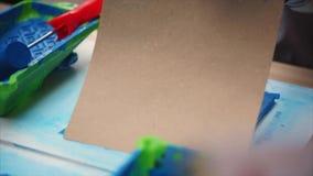 Bambino che disegna i gatti blu facendo uso del timbro di gomma su cartone stock footage
