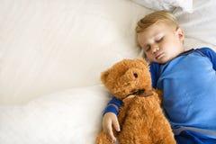 Bambino che dorme con l'orso. Immagini Stock