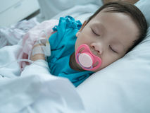 Bambino che dorme nel letto di ammalato in ospedale nella ricezione del dispositivo di venipunzione Immagini Stock Libere da Diritti