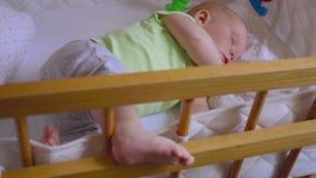 Bambino che dorme nelle greppie: sonno neonato sveglio tranquillamente stock footage