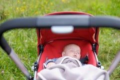 Bambino che dorme in passeggiatore Immagini Stock Libere da Diritti